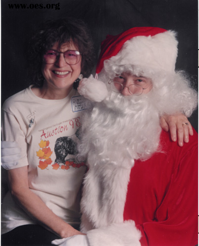 Grannie Annie Raker, Placement Director for New England Old English Sheepdog Rescue, Inc. is Sitting on Santas lap.  Both are laughing.